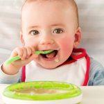 bebe comiendo papilla llena de alimentos nutritivos para su cuerpo