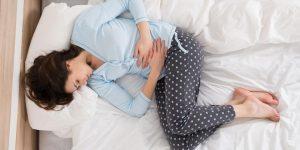 Chica con dolores menstruales en su cama