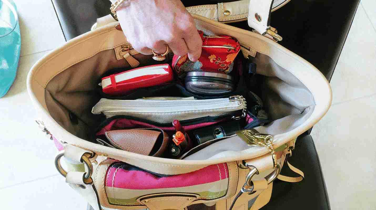 Mujer mostrando el interior de su bolsa