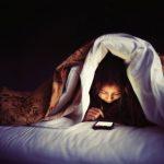 Mujer revisando su celular en la cama