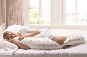 Chica dormida con almohada en cadera