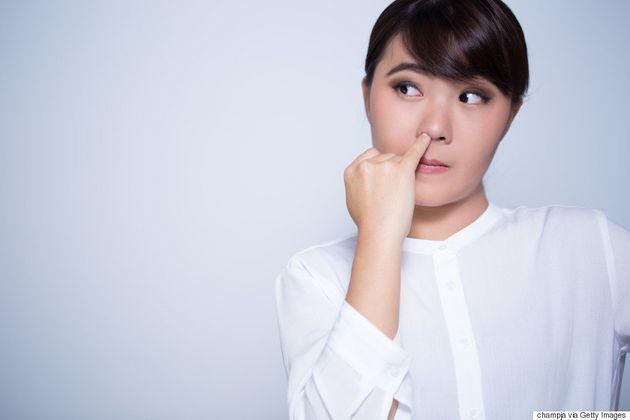 Chica con dedo en la nariz