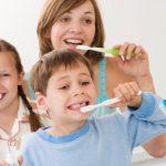 Mamá con sus hijos lavándose los dientes