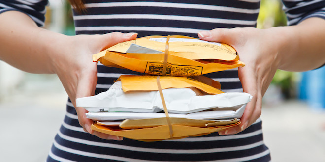 Persona con sobres de paquetería en mano