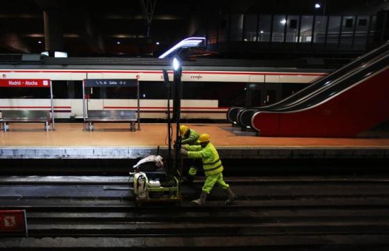 Personas trabajando de noche en vías de tren