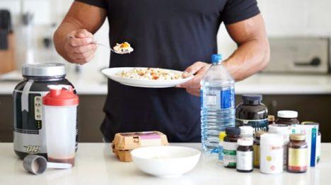 Hombre en la cocina con suplementos