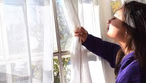 Chica respirando cerca de una ventana